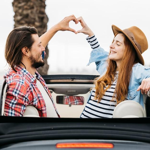Junge lächelnde frau und mann, die symbol des herzens zeigt und sich vom auto heraus lehnt Kostenlose Fotos