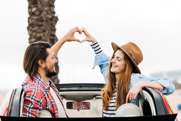 Junge lächelnde frau und mann, die symbol des herzens zeigt und sich vom automobil heraus lehnt Kostenlose Fotos