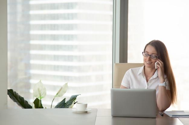 Junge lächelnde geschäftsfrau, die am telefon am arbeitsplatz, mobilkommunikation spricht Kostenlose Fotos