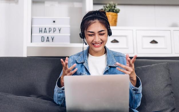 Junge lächelnde glückliche schöne asiatische frau, die unter verwendung der laptop-computerarbeit und videokonferenzbesprechung zu hause entspannt. junge kreative mädchen sprechen mit mit headset. arbeit von zu hause aus konzept Premium Fotos