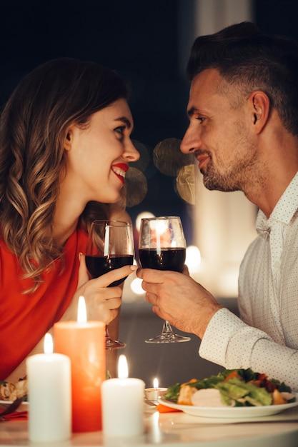Junge lächelnde liebhaber, die einander betrachten und romantisches mit wein und lebensmittel zu abend essen Kostenlose Fotos