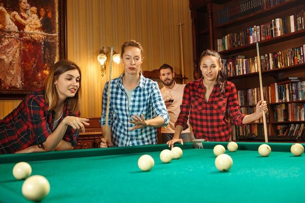 Junge lächelnde männer und frauen, die nach der arbeit billard im büro oder zu hause spielen. geschäftskollegen, die sich mit freizeitaktivitäten beschäftigen. freundschaft, freizeitbeschäftigung, spielkonzept. Kostenlose Fotos