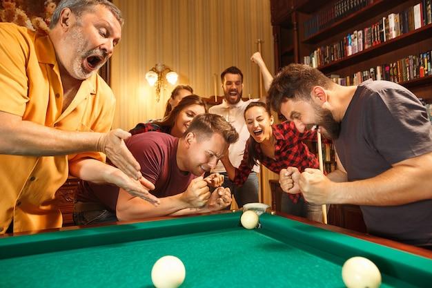 Junge lächelnde männer und frauen, die nach der arbeit billard im büro oder zu hause spielen. geschäftskollegen, die sich mit freizeitaktivitäten beschäftigen. Kostenlose Fotos