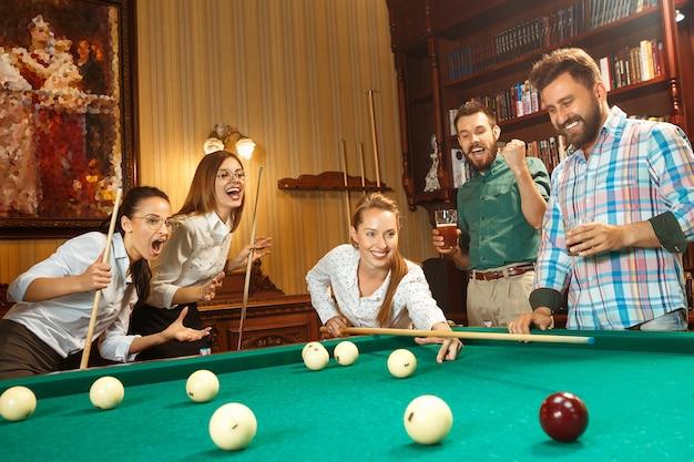 Junge lächelnde männer und frauen, die nach der arbeit billard im büro oder zu hause spielen. Kostenlose Fotos