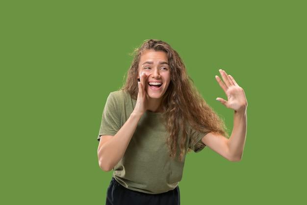 Junge lässige frau, die schreit. schreien. emotionale frau, die auf grünem studiohintergrund schreit. weibliches porträt in halber länge. Kostenlose Fotos