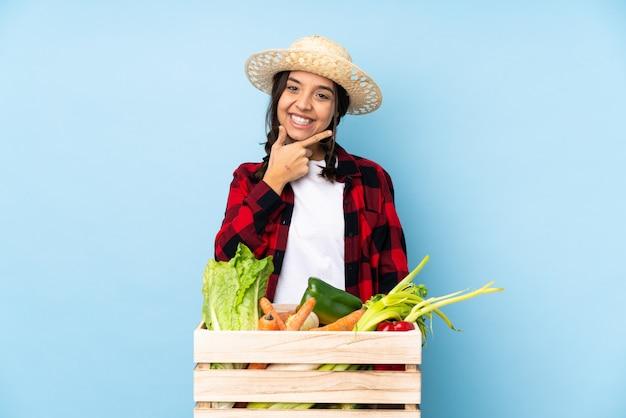 Junge landwirt frau, die frischgemüse in einem hölzernen korblächeln hält Premium Fotos