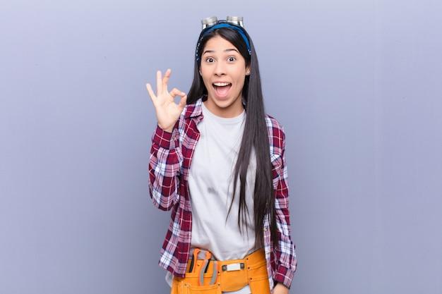 Junge lateinamerikanische frau, die erfolgreich und zufrieden fühlt, mit weit geöffnetem mund lächelt und okay zeichen mit hand macht Premium Fotos