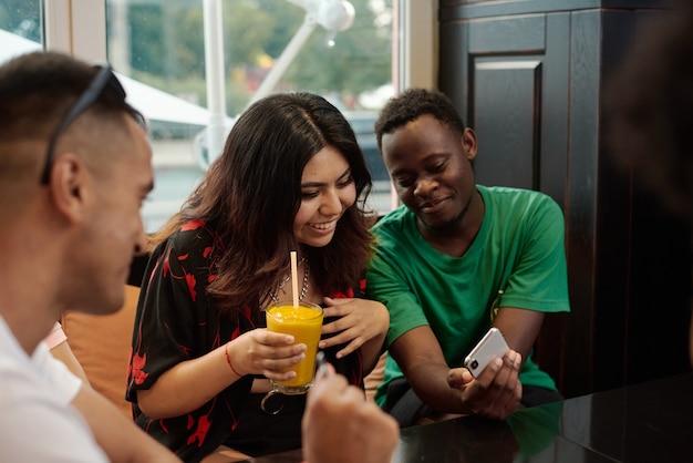 Junge lateinamerikanische frau lacht, während sie auf das telefon ihrer freundin schaut. Premium Fotos