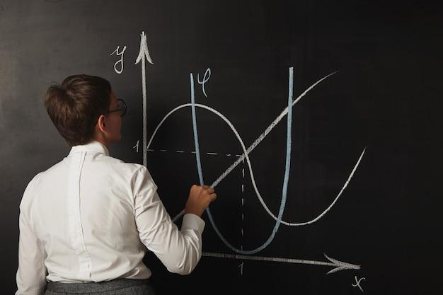Junge lehrerin, die fertig ist, um ihre karte für einen mathematikunterricht an der tafel zu zeichnen Kostenlose Fotos