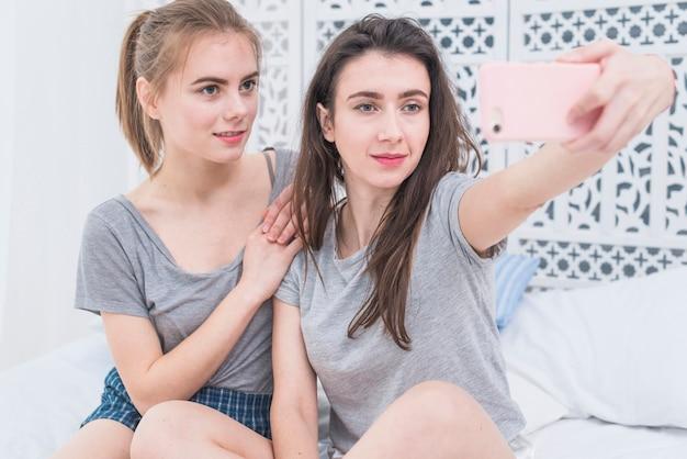 Junge lesbische paare, die auf dem bett nimmt selfie am handy sitzen Kostenlose Fotos