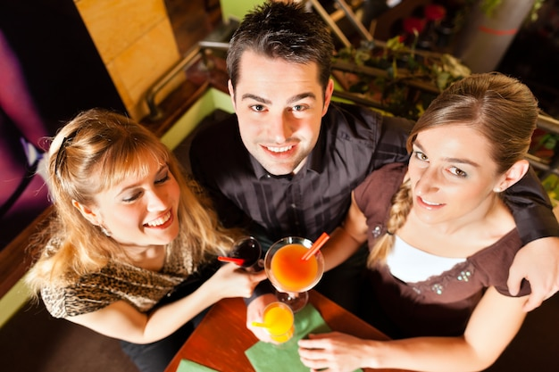 Junge leute, die cocktails in der bar oder im restaurant trinken Premium Fotos