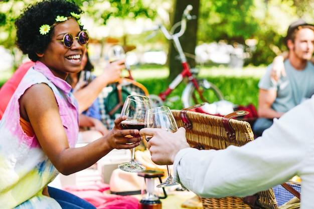 Junge leute, die ein wunderbares picknick in einem park haben und den freudigen moment des trinkens und essens genießen - glückliche freunde, die gläser wein rösten - afro-hipster-frau, die mit ihren freunden jubelt Premium Fotos