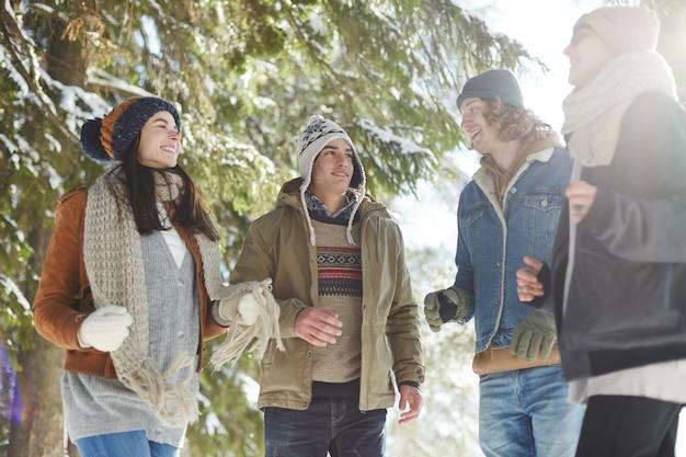 Junge leute, die in winterwald gehen Kostenlose Fotos