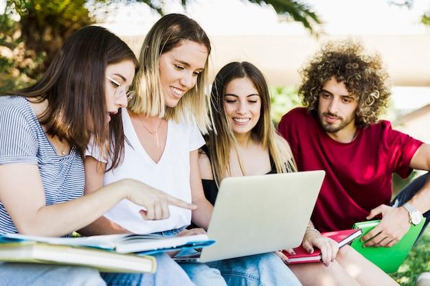 Junge leute, die laptop im park verwenden Kostenlose Fotos