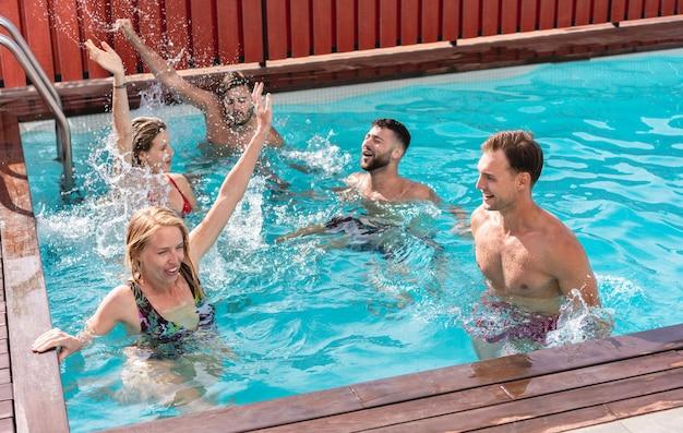 Junge leute, die spaß in der exklusiven villa-party im schwimmbad haben Premium Fotos
