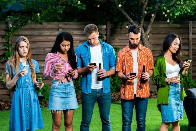 Junge leute draußen mit dem telefonsimsen Kostenlose Fotos