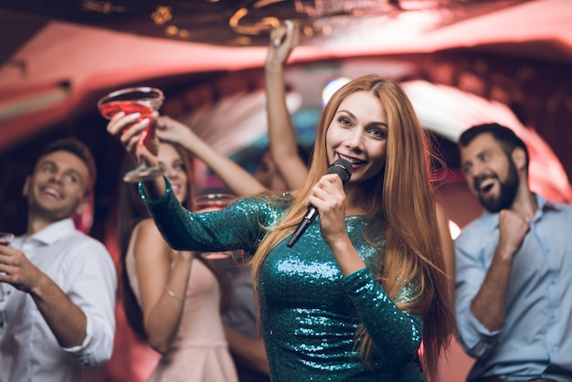 Junge leute haben spaß in einem nachtclub und singen karaoke. Premium Fotos