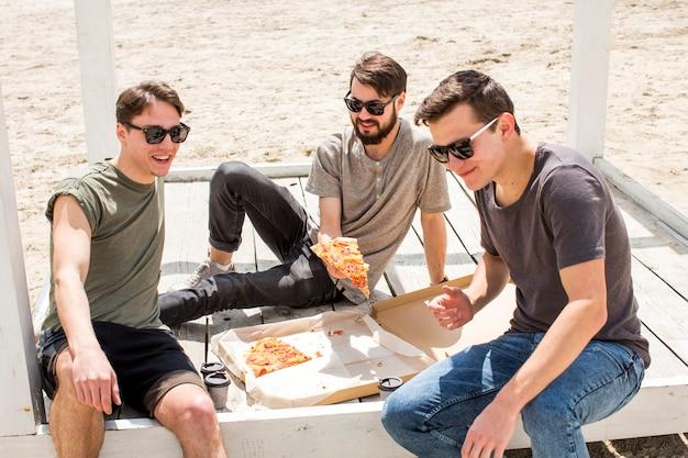 Junge leute mit pizza am strand ausruhen Kostenlose Fotos