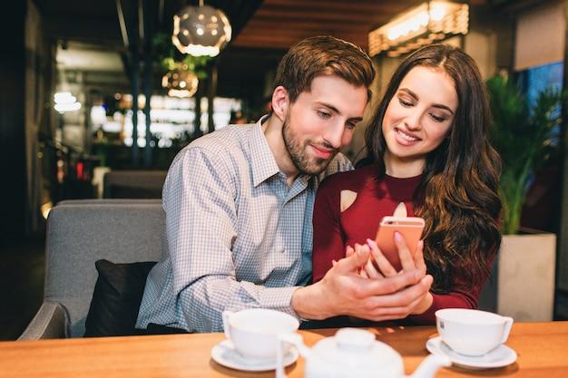 Junge leute sitzen zusammen im café und schauen zum telefon. sie sehen glücklich und ruhig aus. Premium Fotos