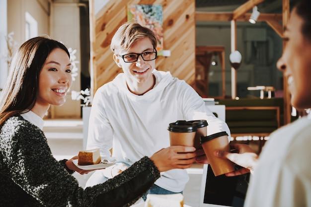 Junge leute trinken kaffee im büro mit freunden Premium Fotos