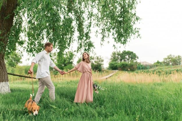Junge liebespaare, die spaß haben und auf dem grünen gras auf dem rasen mit ihrem geliebten inländischen hunderasse spürhund und einem blumenstrauß von wildblumen laufen Premium Fotos