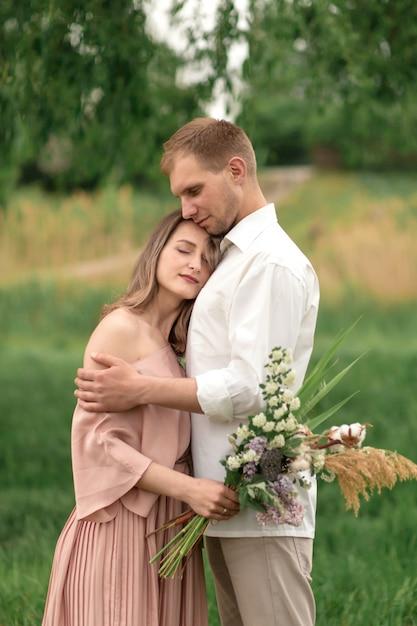 Junge liebevolle paare, die auf das grüne gras auf dem rasen umarmen und tanzen. schöne und glückliche frau und mann berühren sich leicht. schönes paar verliebt. mädchen im kleid und der mann im hemd Premium Fotos