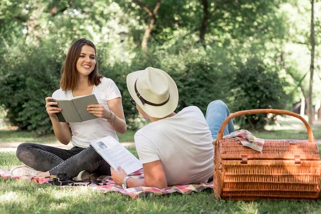 Junge liebhaber, die im park lesen Kostenlose Fotos