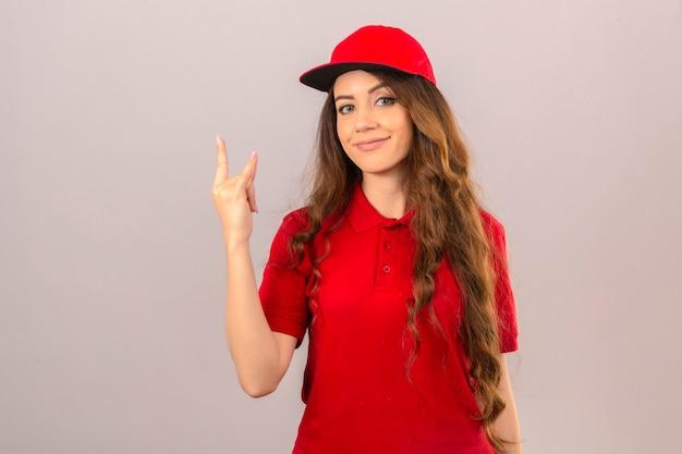 Junge lieferfrau, die rotes poloshirt und mütze trägt junge lieferfrau, die rotes poloshirt und mütze trägt, die mit pizzakästen steht, die freundlich über lokalisiertem weißem hintergrund über isoliert lächeln Kostenlose Fotos