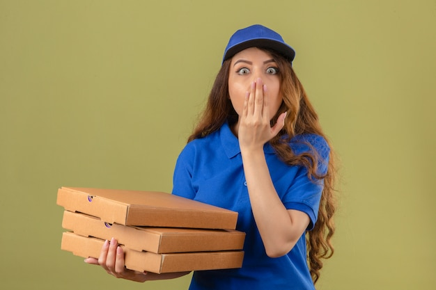 Junge lieferfrau mit dem gelockten haar, das blaues poloshirt und kappe mit stapel von pizzaschachteln trägt, schockierte das abdecken des mundes mit der hand, die mit weit geöffneten augen über lokalisiertem grünem hintergrund steht Kostenlose Fotos
