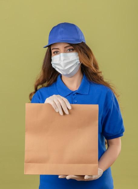 Junge lieferfrau mit lockigem haar, das blaues poloshirt und kappe in der medizinischen schutzmaske trägt, die mit papierpaket steht, das beiseite mit ernstem gesicht über lokalisiertem grünem hintergrund schaut Kostenlose Fotos
