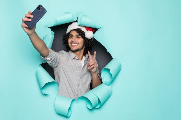 Junge lockige gutaussehende mann tragen in weihnachtsmütze nehmen selfie vom loch auf grünem papier Kostenlose Fotos