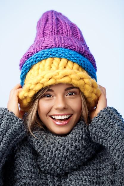 Junge lustige schöne blondhaarige frau in den strickmützen und im pullover, die auf blau lächeln. Kostenlose Fotos