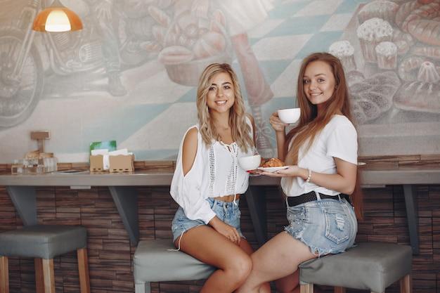 Junge mädchen der mode, die in einem café sitzen Kostenlose Fotos