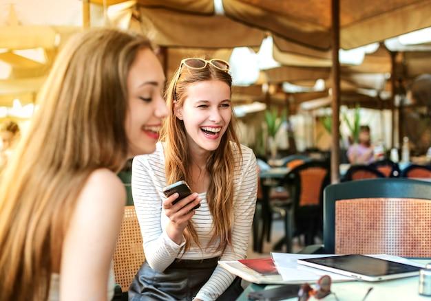 Junge mädchen, die auf der terrasse eines cafés lachen Premium Fotos