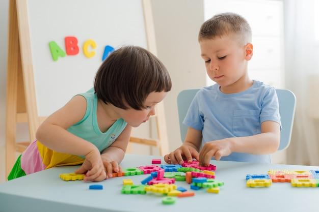 Junge mädchen sammeln weiches puzzle am tisch. bruder schwester viel spaß beim spielen zusammen raum. Premium Fotos