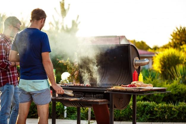 Junge männer, die grill auf grill in der häuschenlandschaft braten. Kostenlose Fotos