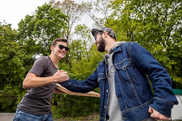 Junge männer, die in der natur sich begrüßen Kostenlose Fotos
