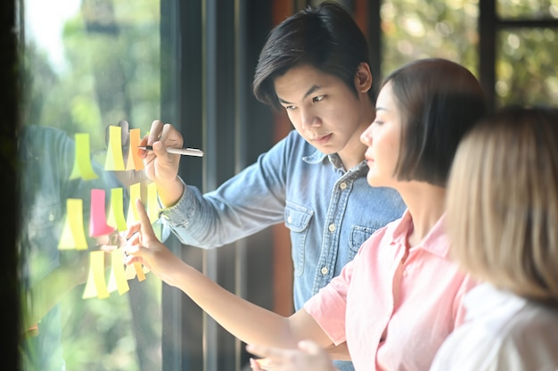 Junge männer und frauen im büro arbeiten zusammen. sie verwenden einen stift und eine hand, um die notiz auf das glas zu zeigen. Premium Fotos