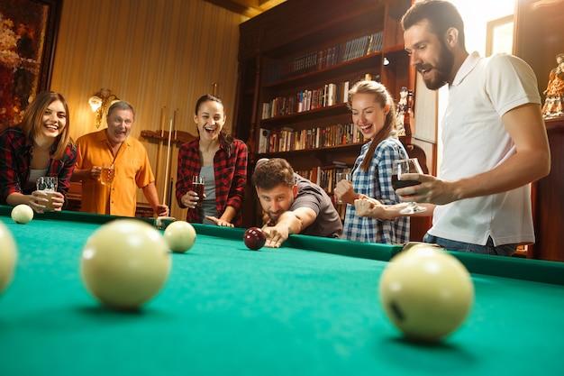 Junge männer und frauen spielen billard im büro nach der arbeit. Kostenlose Fotos