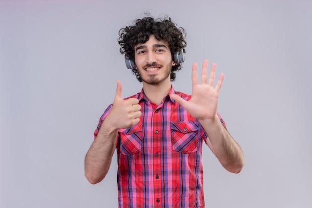 Junge männliche lockige haare isolierten bunte hemdkopfhörer sechs finger Kostenlose Fotos