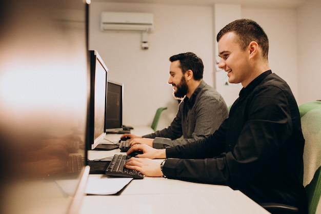 Junge männliche webdesigner, die an einem computer arbeiten Kostenlose Fotos