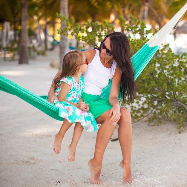 Junge mama und kleines mädchen auf den tropischen ferien, die in der hängematte sich entspannen Premium Fotos