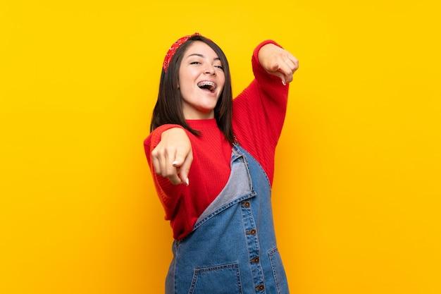 Junge mexikanische frau mit overall über gelber wand zeigt finger auf sie beim lächeln Premium Fotos