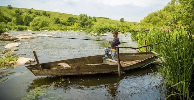 Junge mit angelrutenfischen in einem holzboot Kostenlose Fotos