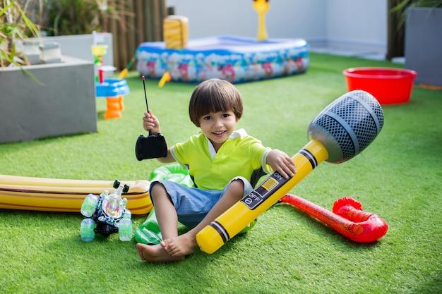 Junge mit aufblasbarem mikrofon. aufblasbares spielzeug für den sommer Premium Fotos