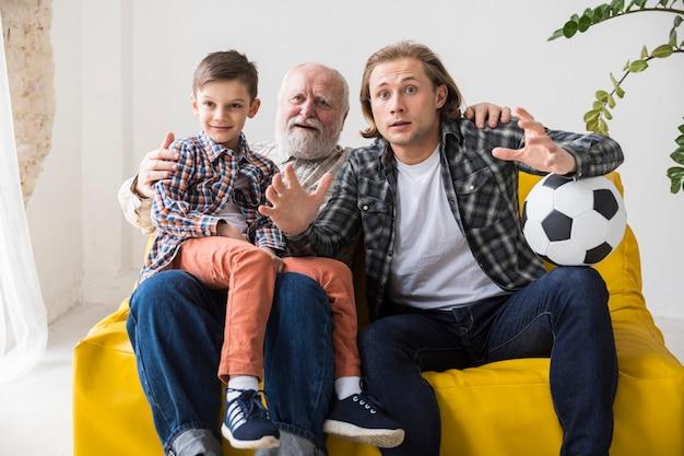 Junge mit aufpassendem fußball des vaters und des großvaters zu hause Kostenlose Fotos