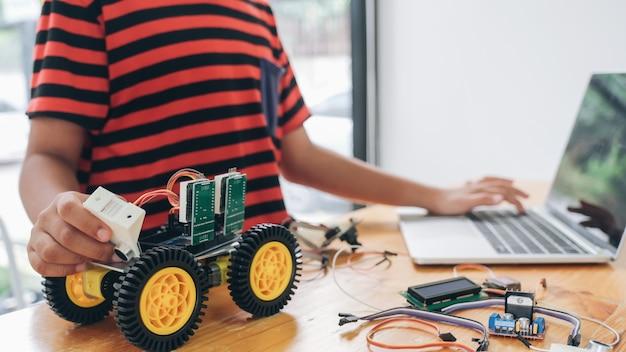 Junge mit dem tablet-pc-computer, der elektrische spielwaren programmiert und roboter errichtet. Premium Fotos
