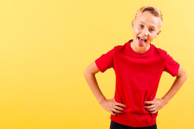 Junge mit den händen auf der taille, die zunge zeigt Kostenlose Fotos