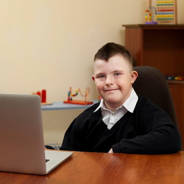 Junge mit down-syndrom posiert mit laptop Kostenlose Fotos