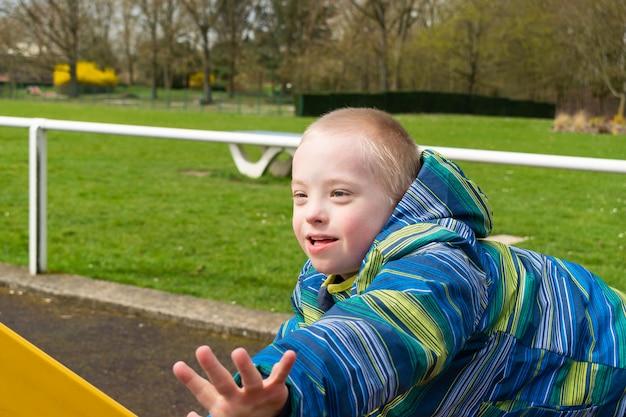 Junge mit einem down-syndrom, das auf einem spielplatz spielt Premium Fotos